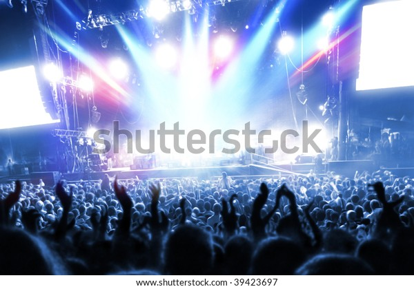 Party people at a frenetic pop concert - landscape exterior