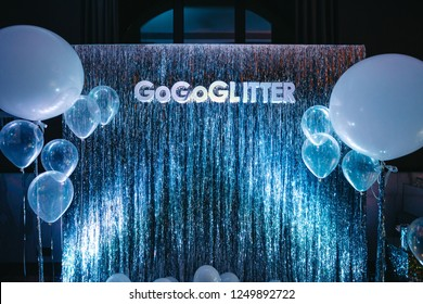 Party photo zone. White and blue balloons hang before sparkling silver wall with lettering 'GoGoGlitter'