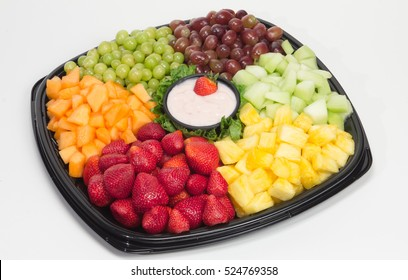 Party platter of fresh fruit: strawberry, cantaloupe, pineapple, grapes and melon served with small bowl of yogurt dip in middle - shot on white background.