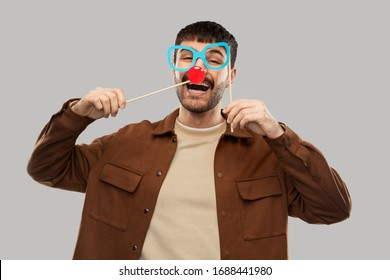 party props, photo booth and people concept - happy smiling young man with paper glasses and red clown nose over grey background