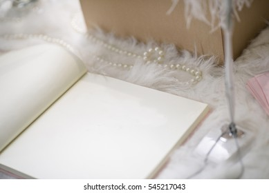 party registration book on white fur table with feather pen and pearl necklace