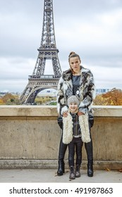 The Party Season in Paris. Full length portrait of trendy mother and daughter in the front of Eiffel tower in Paris, France