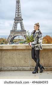 The Party Season in Paris. Full length portrait of trendy woman with Christmas tree in fur coat against Eiffel tower in Paris, France