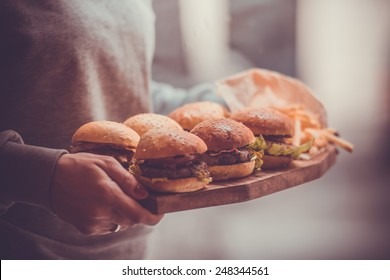 Party set of different burgers on wooden board. Toned image