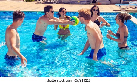 Party at smimming pool. Group of cheerful couples friends playing water volleyball. Happy youth time