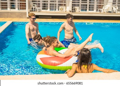 Party at smimming pool. Men and women playing in the pool with swimming circles and Swimming mattress. Summer rest and vacation