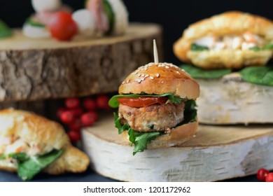 Party snacks, mini burgers, croissants and sandwiches, rustic wooden decor