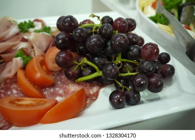 Party snacks such as grapes, salami, smoked ham, other sausages, tomatoes, parsley, on a buffet on a birthday celebration party as a starter on a white plate