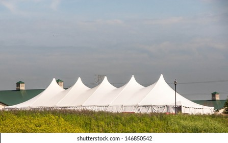 Party Tent or a big white banquet wedding tent for ceremonies. White tent against blue sky.