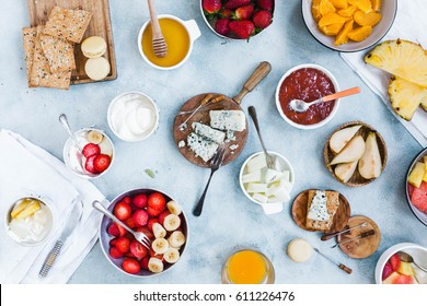 Party time. Gorgonzola cheese, fruits, snacks and yogurt bowls over brunch table. Gourmet breakfast table.