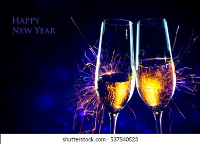 Party time with two champagne glasses and fireworks of sparklers against a dark blue background with sample text Happy New Year