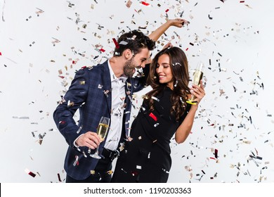 Party for two! Young beautiful couple bonding and dancing while standing against white background with confetti