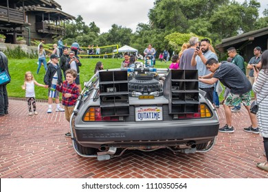 """Pasadena, CA: May 20, 2018: A DeLorean parked in front of the Gamble House, with Back to the Future fans present, in Pasadena.  The Gamble House was featured in the cult favorite """"Back to the Future."""""""