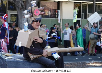 """Pasadena, CA / USA - Nov. 24, 2019: A man sits on a car, with a cardboard gun and armor, at the Pasadena Doo Dah Parade, which has been billed as """"an irreverent alternative to the Rose Parade."""""""