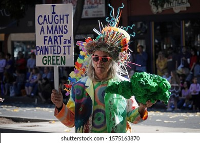 """Pasadena, CA / USA - Nov. 24, 2019: A man holding a quirky sign reading """"I caught a mans fart and painted it green"""" is shown at the """"42nd Occasional"""" Pasadena Doo Dah Parade."""