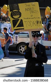 """Pasadena, CA / USA - Nov. 24, 2019: A woman is shown holding a sign that reads """"Join the Armed Farces at toysoldiersunite.com today!!!"""" at the 42nd annual Pasadena Doo Dah Parade."""