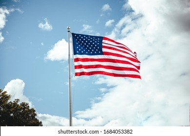 Pasadena, California / USA - March 25, 202: The United States flag blowing in the wind on a warm sunny day at a local store in Pasadena. A sign of freedom during the coronavirus pandemic