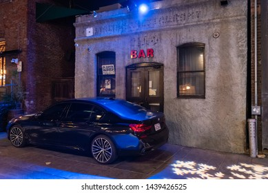 PASADENA, CA/U.S.A. - JANUARY 4, 2019:  A moody urban night photo of a parked BMW car in front of an unnamed concrete bar with a red sign and blue light.