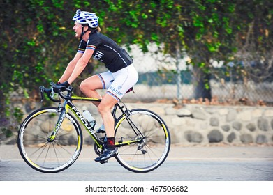 PASADENA/CALIFORNIA - AUG. 11, 2016: Isolated cyclist out on an enthusiastic ride on a summer evening in Pasadena, California USA
