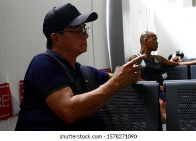 Pasay Ciy, Philippines – November 27, 2019: Adult Filipino man use his smartphone to pass the time while at a waiting area of an airport.