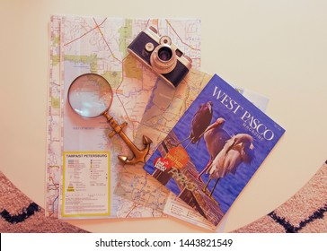 Pasco, FL USA 07/06/2019 Illustrative Editorial of West Pasco Magazine, Nautical Magnifying Glass and Argus Old Film Camera over Top Of a Map Of Tampa Area and Hillsborough County on Plain White Table