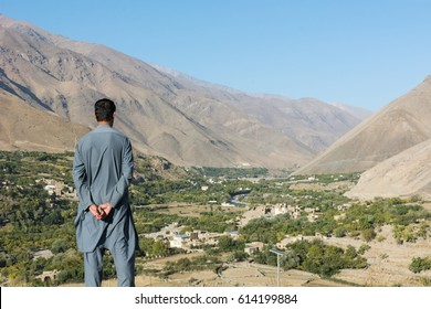 A Pashtun man in gray traditional salwar kameez clothes from behind standing thoughtfully looking out over the green Panjshir Valley near Kabul, Afghanistan on a sunny day