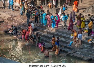 Pashupatinath sacred Hindu Temple, Kathmandu, Nepal-October 18, 2018: Devoted Hindu women and men taking what is believed  a holy bath in Bagmati river to wash away sins