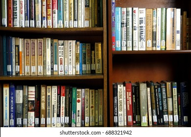 PASIG CITY, PHILIPPINES - JULY 31, 2017: A wide variety of books on wooden shelves inside a library.