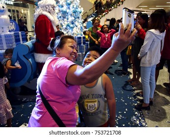 PASIG CITY, PHILIPPINES - NOVEMBER 12, 2017: Customers takes a selfie in front of a christmas display of a commercial establishment.