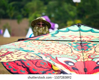 Pasir Gudang, Malaysia - March 1, 2018: Kite flyer ready to launch a kite with traditional Indonesian pattern at the Pasir Gudang World Kite Festival in the Johor State of Malaysia.