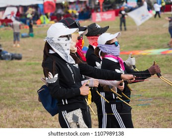 Pasir Gudang, Malaysia - March 1, 2018: Female, Chinese stunt flying team performing formation flying with 4-line kites at the Pasir Gudang World Kite Festival in the Johor State of Malaysia.
