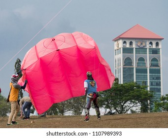 Pasir Gudang, Malaysia - March 3, 2018: Two Indonesian kite flyers launching their big, pink parafoil kite at the Pasir Gudang World Kite Festival in the Johor State of Malaysia.