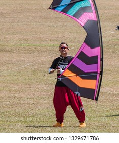 Pasir Gudang, Malaysia - March 3, 2019: Chinese kite flier Yao Qingshan flying a quad line kite on short lines at the 24th Pasir Gudang World Kite Festival with participants from 43 nations.