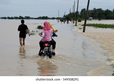 Pasir Puteh, Kelantan, Malaysia - 4th January 2017 : A man and motorcyclist went through the flood that has risen and covered the road.