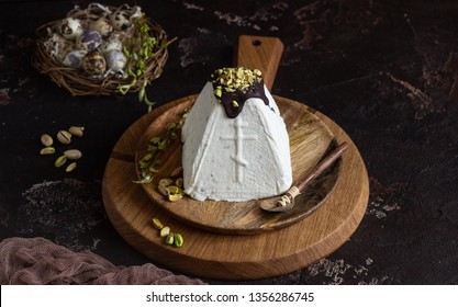 Paskha (Pasha) with pistachios decorated with chocolate glaze and pistachios. Traditional Russian orthodox Easter quark dessert. Easter food background.