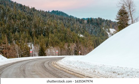 Pass road between snowy hills, mountain  in the background, blind corner, right turn