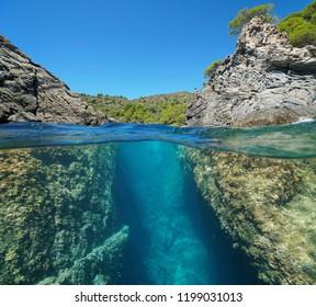 A passage between rocks on the seashore, split view above and below water surface, Spain, Mediterranean sea, Costa Brava, Roses, Catalonia, Girona