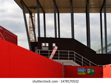passageway at large construction site of red temporary walls, corridor for pedestrians