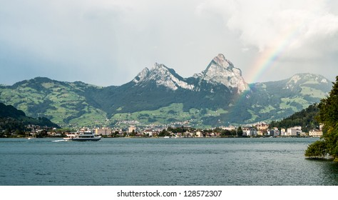 A passanger ship sails to the city on the other side of the Lucerne lake while rainbow shines in the sky next to mountains