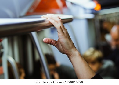 Passangers holding the hand rail on crowded public transports. Rush hour. Travel in the subway. Unhygienic and risk of transmitting germs