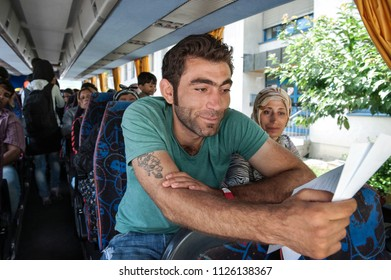 Passau, Germany - August 1, 2015: A refugee from Syria is deeply relieved after registering on the bus on the way from Passau. He is seeking asylum in Europe