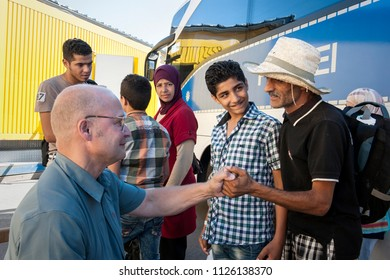 Passau, Germany - August 1, 2015: A refugee thanks a german doctor for taking care of him at the registry camp in Passau.