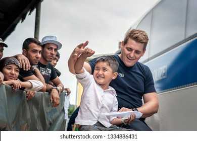 Passau, Germany - August 1, 2015: A German policeman jokes with a little Syrian refugee boy at the registration center in Passau, Germany.