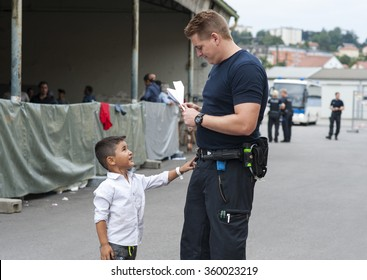 Passau, Germany - August 1, 2015: A german police officer takes care of a little refugee child from Syria in the registration area of Passau.