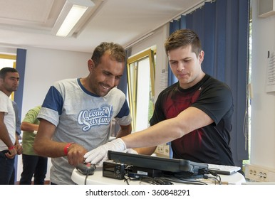 Passau, Germany - August 1, 2015: A police officer takes the finger print of a man during his registration at theregistration center for migrants and refugees of the southern German border town Passau