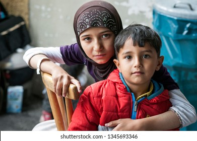 Passau, Germany - August 1st, 2015: Syrian refugee sister and brother at a camp in Passau, Germany. The police and several organisations try to push them through registration fast in order.
