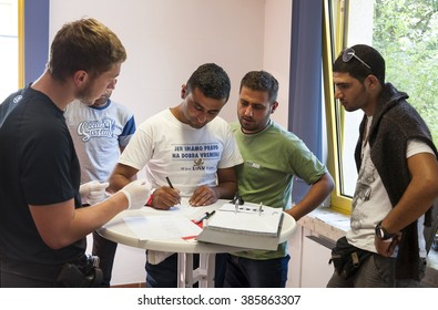 Passau, Germany - August 1th, 2015: A police officer takes the signature of a man during his registration at the temporary registration center for migrants and refugees of the  town Passau in Germany