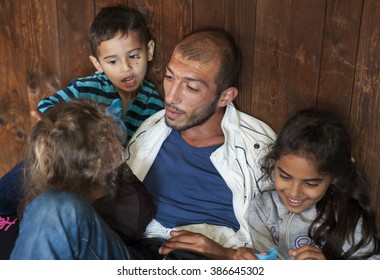 Passau, Germany - August 2, 2015: Father and his three young children in migrant registration center in Passau, southern Germany,