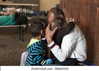Passau, Germany - August 2, 2015: Father and his three young children from Syria in migrant registration center in Passau, southern Germany