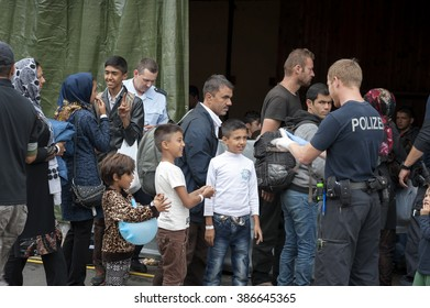 Passau, Germany - August 2, 2015:  A German police officer is taking care of refugees at the registration area in Passau, Bavaria.
